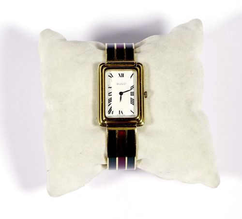 ENAMEL LADY'S WRISTWATCH, GUCCI, 1970s. Yellow gold 750, 95g. Rectangular case No. 1025 with fluted lunette. White dial with Roman numerals and blued hands. hand winder, Cal. ETA 2512. Decorative, two-part bangle bracelet with 3 band motifs enamelled in burgundy and green. Clasp designed as a belt buckle. L ca. 18.5 cm.