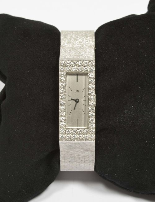 DIAMOND LADY'S WRISTWATCH, UTI, ca. 1960. White gold 750, 60g. Rectangular case integrated in the band, lunette pavé-set with 44 brilliant-cut diamonds weighing ca. 1.30 ct. Silver-coloured dial with black indices and hands, signed UTI. Hand winder, form movement Cal. FHF59-21, signed Ebel Watch. Finely textured Milanaise band, L ca. 18.5 cm. D 33 x 15 mm.