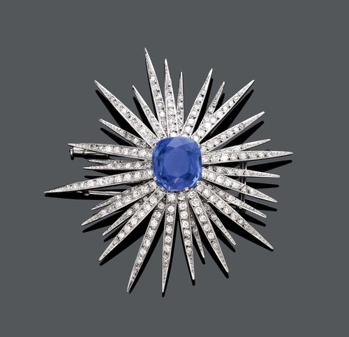 BURMA SAPPHIRE AND DIAMOND CLIP BROOCH, IGOR FABERGÉ, ca. 1950. White gold 750. Fancy, star-shaped brooch, the centre set with 1 antique-oval, fine Burma sapphire weighing ca. 11.00 ct, unheated, minimal signs of wear, the 30 rays set throughout with numerous brilliant-cut diamonds and single-cut diamonds weighing ca. 3.00 ct in total. Ca. 6.3 x 6 cm. Oral short report by GGTL/Gemlab.