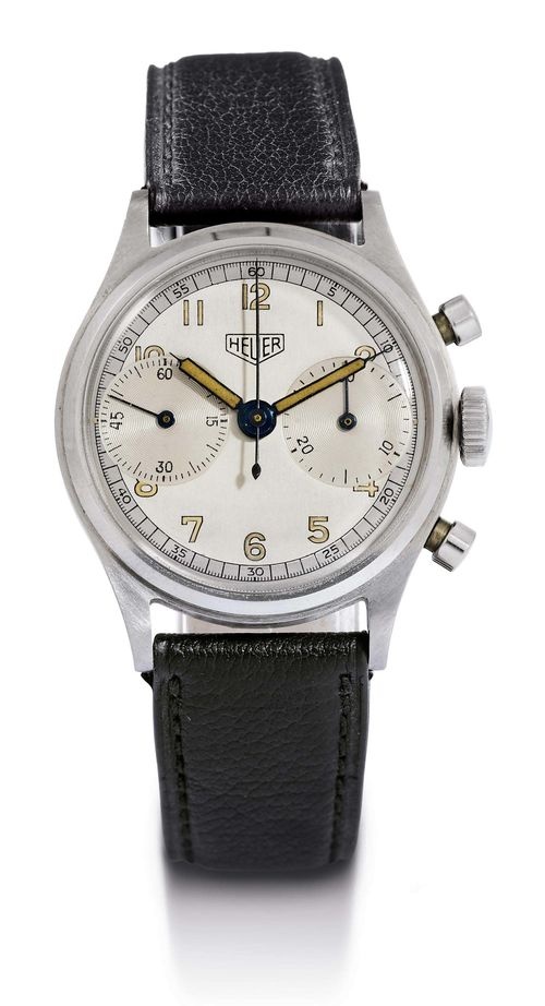 HEUER CHRONOGRAPH WITH 30 MINUTE COUNTER AND ORIGINAL SALES LABEL, 1940s. Stainless steel. Almost unworn, polished case No. 68438. Screw-down back signed: Ed. Heuer & Co, Swiss, stainless steel. Silver-coloured, two-tone dial with luminous Arabic numerals and luminous hands. Signed HEUER, minute counter at 3h, small second at 9h. Hand winding movement No. 407301. Valjoux Cal. 23, with shock protection, screw balance wheel with Breguet spring. Black leather band with clasp. D 35 mm.