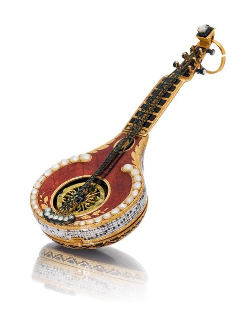 """RARE CYLINDER WATCH WITH EXQUISITE ENAMEL WORK. Gold, enamel, and half-pearls. Case designed as a mandolin, engraved, red enamelled and set with half-pearls, the open centre with engraved skeleton balance bridge, the handle enamelled black, one lateral part missing. The back engraved and enamelled burgundy, sprung cover with small flower in gold with blue and green enamel. The side of the mandolin with a very fine enamel miniature depicting the notes of the aria by Nicolas-Medard Audinot (1732-1801) """"Le Tonnelier"""" from the Comical Opera 1761 and the text: """"un tonnelier vieux et jaloux"""" in black on a white ground. Enamelled dial with Arabic numerals, pink gold hands, and winder at 2h. Miniature cylinder movement with skeleton bridge and small regulator scale, fusee and chain. Enamel, in part restored. D 64 x 26 mm."""
