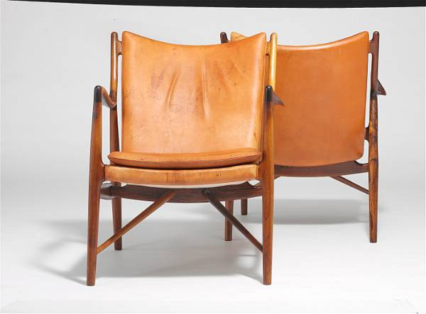 """Finn Juhl: """"FJ 45"""". A pair of Brazilian rosewood easy chairs. Sides, back and loose seat cushion upholstered with patinated brown leather. (2)"""