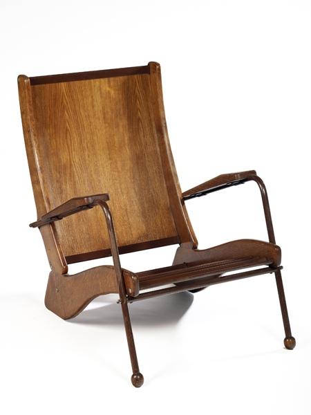 Jean PROUVÉ (1901-1984) Fauteuil modèle 'Kangourou' à structure en métal tubulaire laqué brun et chêne patiné, à dossier plein, accotoirs et pieds boules en chêne, assise en tôle ondulée se prolongeant dans le piétement arrière. Haut. 84,5cm - Larg. 66cm - Prof. 100,5cm