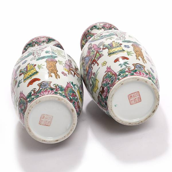 A pair of 20th century Chinese porcelain vases decorated in enamel colours with scholars and precious things. H. 26 cm. (2)
