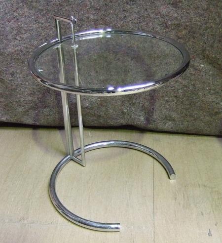(D'après EILEEN GRAY). Un guéridon de forme circulaire constitué de tubes de métal chromé, plateau ajustable centré d'une vitre, Edition Ecart International. Haut. minimal 63 cm, diam. 51 cm.
