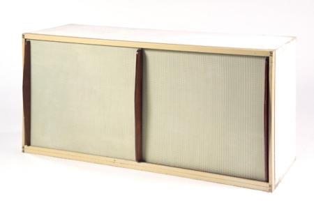 Jean PROUVÉ (1901-1984) Buffet bas, structure parallélépipédique en bois laqué blanc, façade formée de montants parallélépipédiques laqués ivoire, maintenant une structure en bois accueillant deux portes coulissantes en bois plaqué de feuilles d'aluminium présentant un semis de pointes de diamant de teinte vert amande, découvrant un intérieur aménagé d'étagères, cloison médiane et crémaillères latérales en métal laqué ivoire, prises verticales en frêne profilé teinté acajou, cabochons de laiton en relief en façade. Haut. 86cm - Long. 170cm - Prof. 61cm
