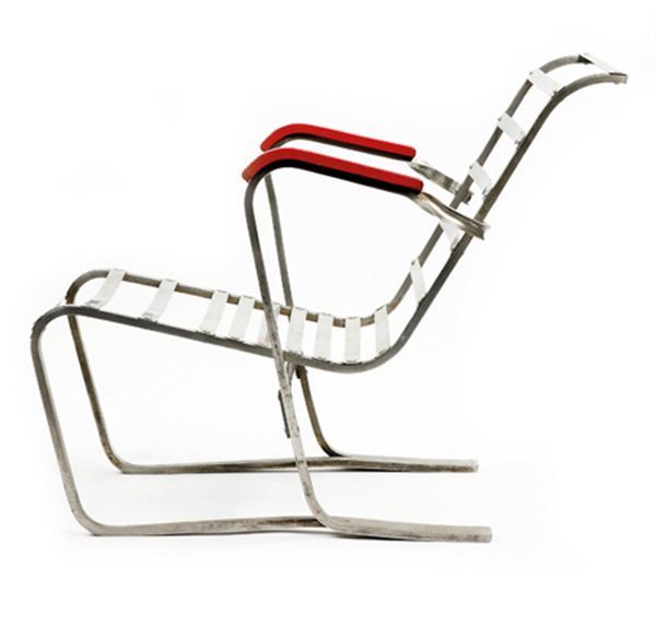 MARCEL BREUER (1902-1981) & STYLCLAIR Fauteuil bas, structure profilée en duralumin, le piétement est formé à l'arrière d'une bande se détachant en deux parties, l'une formant structure d'assise et dossier, l'autre formant soutien d'accotoirs, rejoignant le dossier par un mouvement vrillé. L'assise et le dossier sont tendus de lames d'aluminium rivetées à une structure en gorge venant compléter la structure rainurée principale. Accotoirs relaqués rouge. Étiquette 'Meuble Stylclair Paris Lyon', n° estampé '311'. Haut. 69,5cm - Larg. 58cm - Long. 81cm