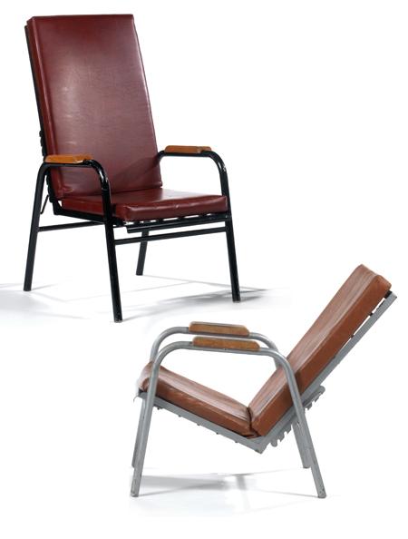 Jean PROUVÉ (1901-1984) Suite de deux fauteuils de repos, à structure métallique tubulaire laquée noir pour l'un et gris pour l'autre, double arcature constituant piétement et accotoirs. Structure profilée en V formant assise et dossier, une crémaillère dorsale permet de régler l'inclinaison du siège, coussins d'assise et de dossier en skaï rouge jaspé et cognac pour l'autre. Haut. max 111cm - Larg. 62cm - Prof. max. 100cm