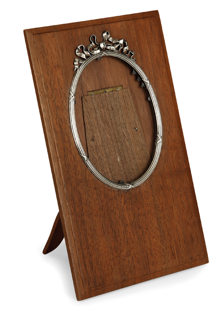 Porte-photos en argent en forme de médaillon ovale surmonté d'un ruban et fixé sur un support en bois agrémenté d'un rabat de présentation. Travail de Fabergé. Haut. 24cm - Larg. 15cm