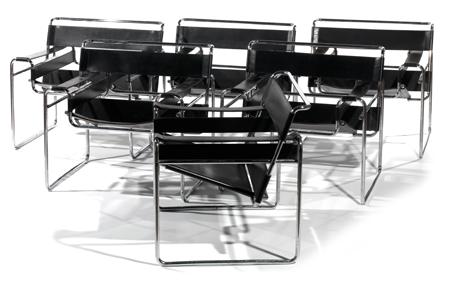 Marcel BREUER (1902-1981) & GAVINA (éditeur) Rare suite de six fauteuils bas, modèle 'Wassily', structure métallique tubulaire chromée formant enchevêtrement d'arcatures géométriques. Assise, dossier et accotoirs tendus de bandes d'épais cuir noir piqué sellier en bordure. Traces d'étiquette d'éditeur. (Quelques usures et éraflures). Haut. 73cm - Larg. 78,5cm - Prof. 68cm