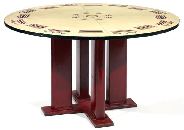 Jean PROUVÉ (1901-1984) & Jules LELEU (1883-1961) Grande table circulaire 'Cible', piétement cruciforme en tôle laquée rouge, formé d'une terrasse en X d'où s'élèvent quatre ailettes animées de ressauts de section carrée à la base, grand plateau supérieur circulaire en bois gainé d'un stratifié blanc cassé à décor d'une frise de motifs géométriques en pourtour et d'une cible stylisée au centre. (Un petit élément à ressouder sous le plateau).  Haut. 73,5cm - Diam. 126cm