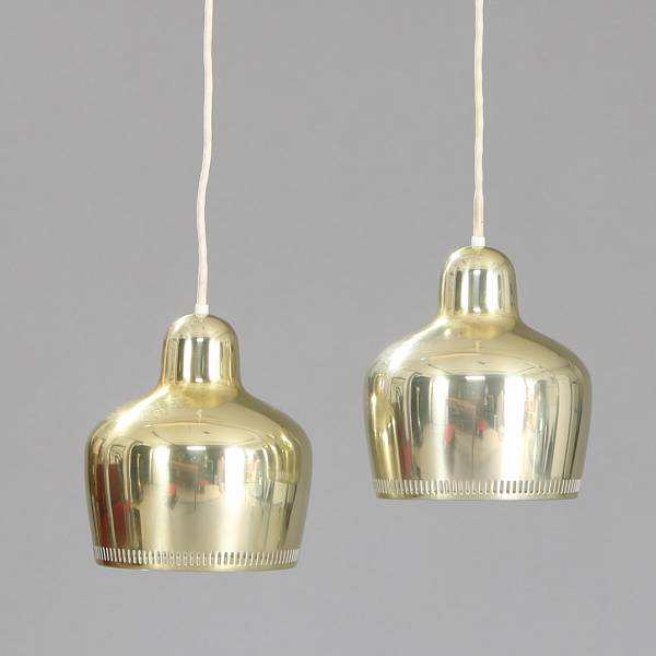 "Alvar Aalto: ""Golden Bell"". A pair of pendants of polished brass, inside with white paint. Model A 330.  Manufactured by Louis Poulsen. Dia. 17 cm. (2)"