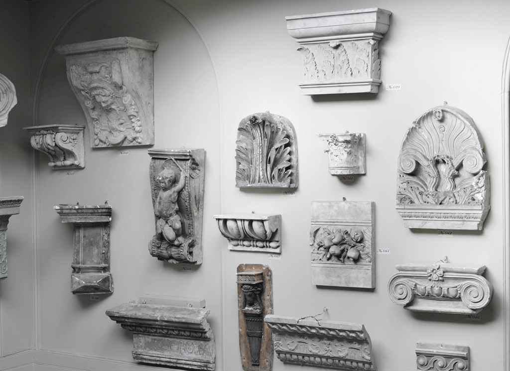A COLLECTION OF FIFTEEN PLASTER CAPITALS, CORBELS AND ARCHITECTURAL FRAGMENTS