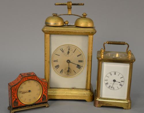 Three desk or alarm clocks to include Kienzle Day enameled clock, a brass and glass carriage clock with enameled dial, and a carriag...