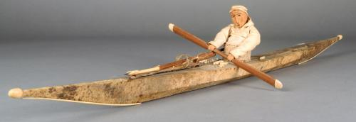 An Inuit model kayak skin and bone with a seated figure with carved wood head and hands holding a pa