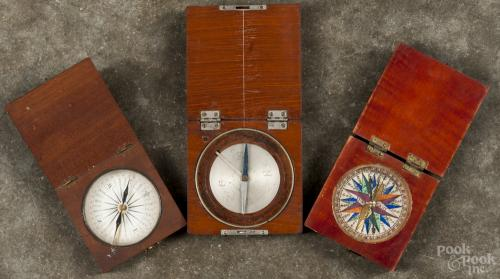 Three small compasses, ca. 1900, the largest signed Queen & Co. Philada., all in wood cases.