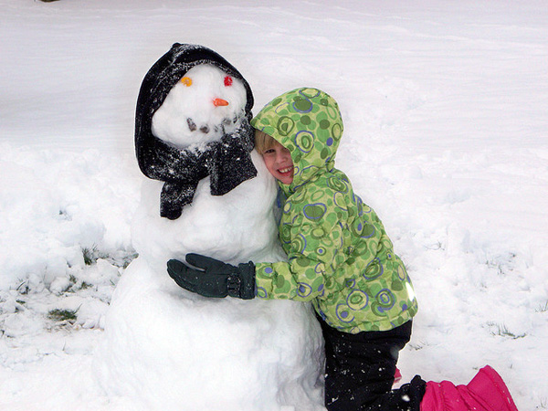 Girl hugging snowman