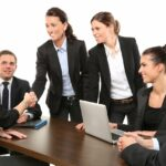 Planejamento de vendas e operações: reunião de negócios, com duas mulheres apertando as mãos ao centro