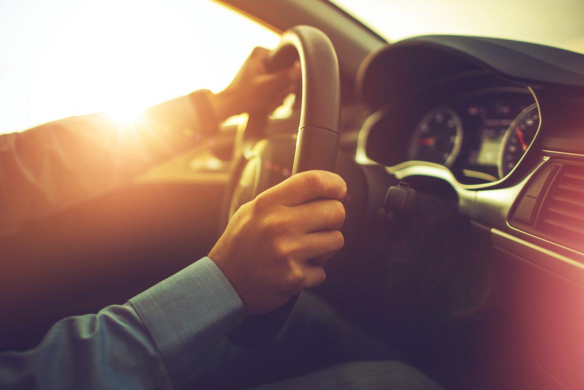 Imagem de mãos segurando volante de carro