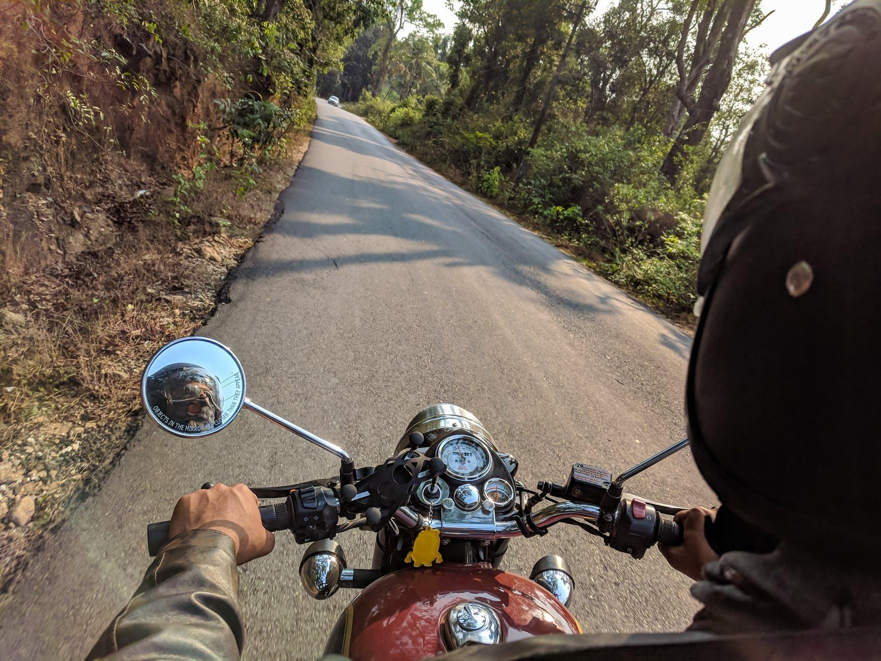 Imagem de estrada e homem pilotando moto
