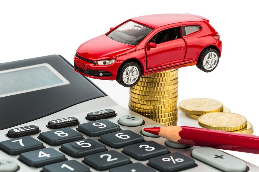 Imagem de miniaturas de lápis, calculadora, carro e moedas.