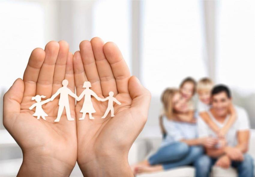 Imagem de mão com desenho representativo de uma família e família ao fundo da imagem