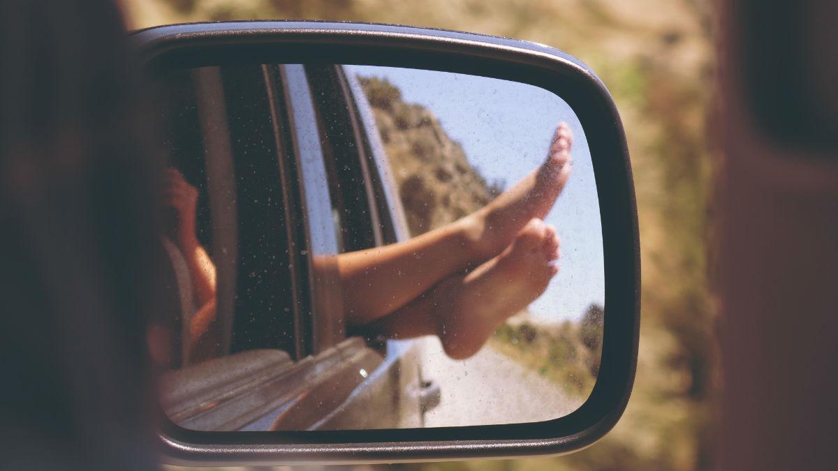 rterovisor com imagem de pés para fora da janela do carro