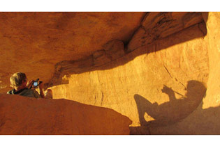 David Coulson photographing a painting under an overhang in Chad. Photographed by Nigel Pavitt.