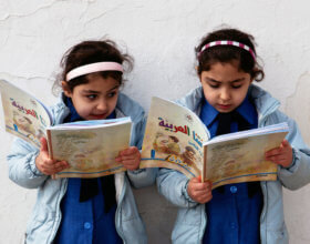 Young girls reading at a public primary school in Amman. (Photo by: Wikimedia)