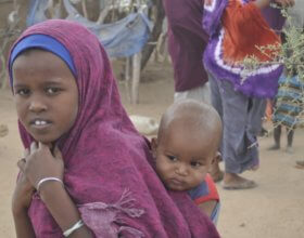 A girl carries a baby past a market in El Wak, a town in southern Somalia (Photo: Doreen Ajiambo).