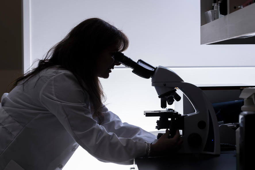 Female Scientist Silhouetted Using Microscope
