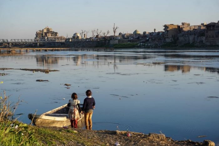 Two girls contemplate the destruction in the Old City of Mosul from across the River Tigris  (Photo: Ali ِal-Baroodi).
