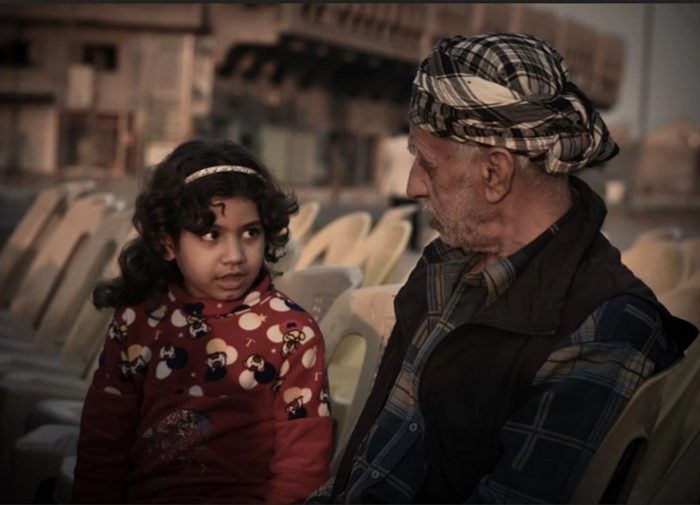 A young girl and an older man chat on a city street (Photo: Ali ِYousif al-Baroodi).