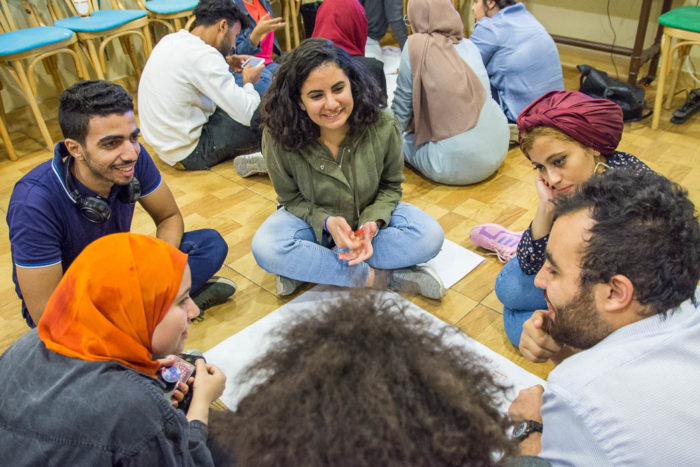 Small groups of students huddle during an environmental awareness training session in Cairo (Photo: Nahdet el Mahrousa).
