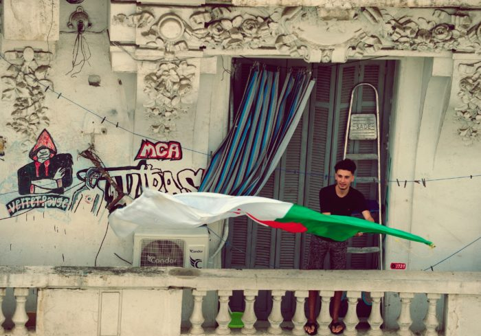 A man waves a flag on a balcony during a demonstration coinciding with the celebration of Algeria's independence from France (Photo: Kadri Mohamed/Sipa/AP).