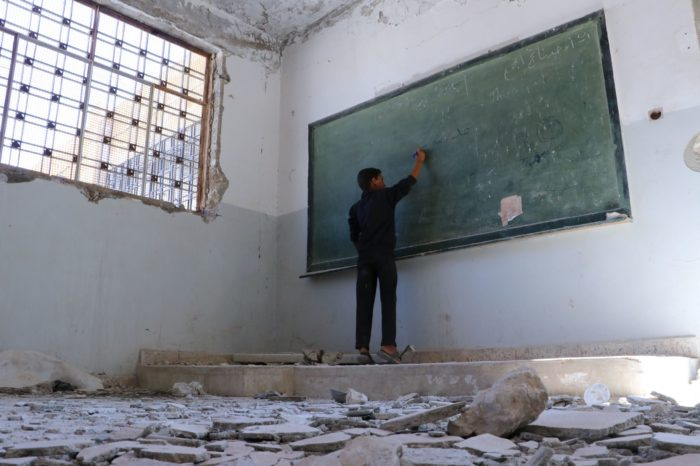 A boy writes on the board of an unused classroom near Idlib, Syria (Photo:Save the Children's partner in Syria, Hurras Network).