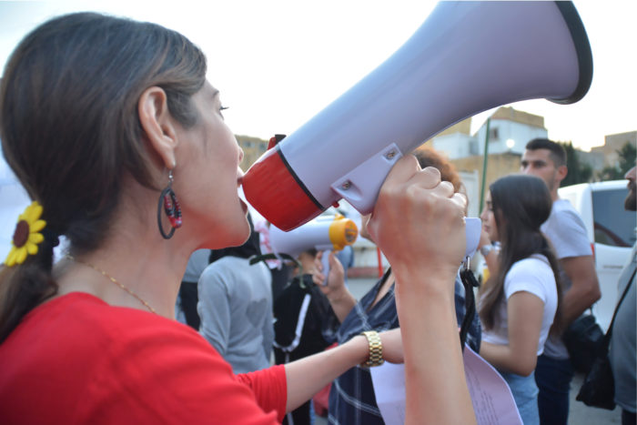 Protesters use megaphones to chant slogans about their goals and to urge others to join them as they walk through the streets (Photo: Tharaa Captan Bchennaty).