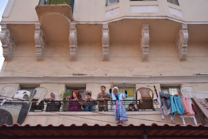 In Tripoli, Lebanon, onlookers on a balcony watch demonstrators who are going by (Photo: Tharaa Captan Bchennaty).
