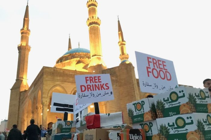 In one of many individual efforts to sustain the protests, a person contributes food and drinks. In the background is Beirut's Mohammad Al-Amin Mosque (Photo: Dana Abed).