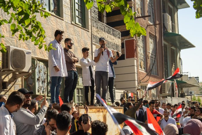 Student protests are carefully planned, with chants screened in advance. Above, Ameer Ahmed, second from left, and other organizers lead chants from a stage before the protesters march to Baghdad's Tahrir Square (Photo by Olivia Cuthbert).