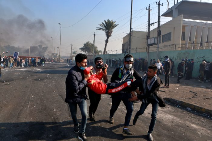 An injured protester is rushed to a hospital in central Baghdad this week, after security forces fired live rounds (Photo: Khalid Mohammed/AP).