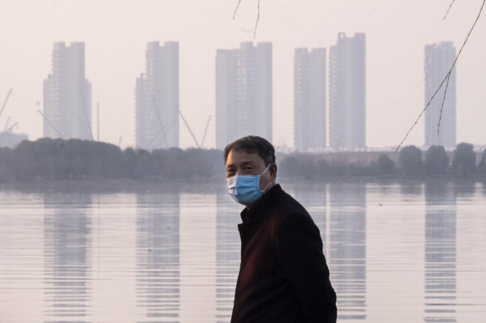 A man walks along the deserted waterfront in Wuhan, China where the coronavirus outbreak appears to have started (Photo:  Arek Rata/AP).