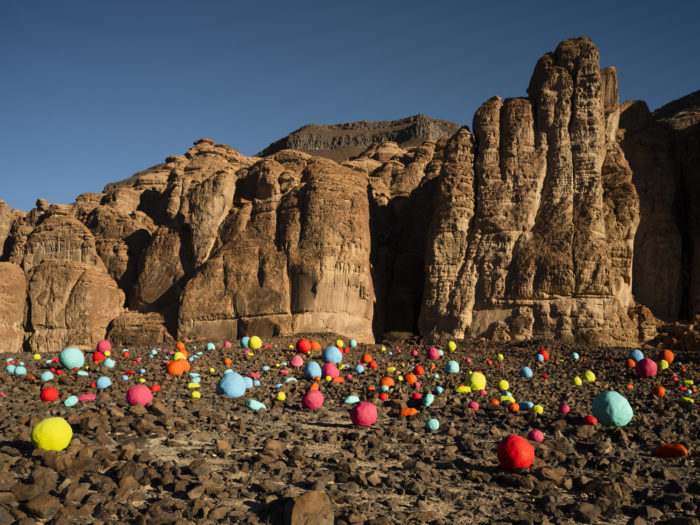 Emirati artist Mohamed Ahmed Ibrahim, known for producing work inspired by the landscape of his native region, produced Falling Stones Garden, an installation of neon-colored spheres (Image courtesy of Lance Gerber, the artist, Lawrie Shabibi, RCU and Desert X).
