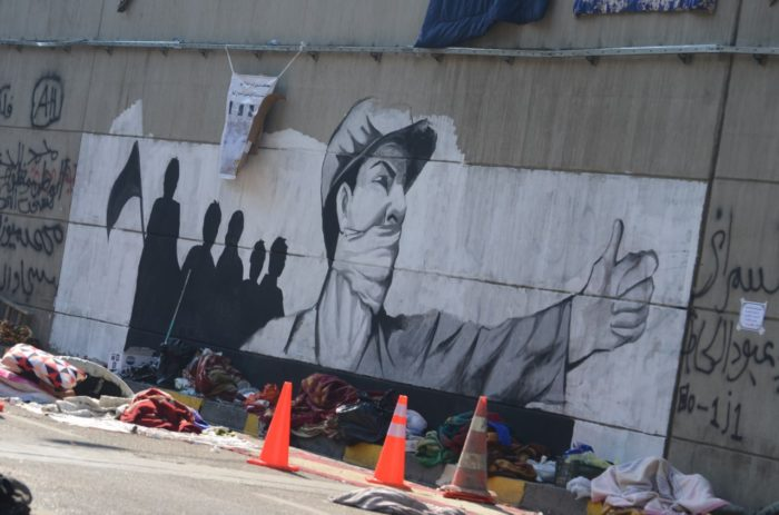 Protesters sleep in Al-Saadoun Tunnel with a Soviet-inspired mural in the background (Photo: Caesar Al-Wardi).