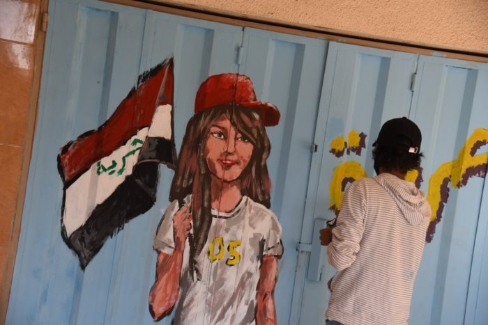 A painting depicts a young woman carrying an Iraqi flag with the word 'Freedom' replacing the religious slogan 'Allahu Akbar,' added by Saddam Hussein in 1991 (Photo: Caesar Al-Wardi).