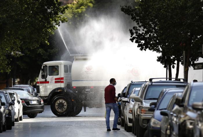 A municipal tanker sprays disinfectant in Beirut. The Lebanese government is beginning to work more closely with public health experts on the coronavirus pandemic (Photo: Hussein Malla/AP).