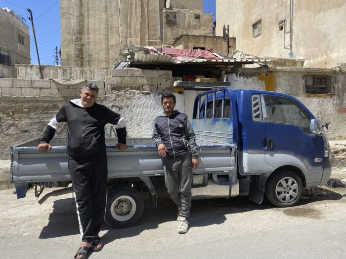 Two brothers pose by a pickup truck in the Palestinian refugee camp of al-Wehdat, in Jordan. Their work as drivers has been interrupted during Jordan's coronavirus lockdowns  (Photo: Omar Akour/AP).