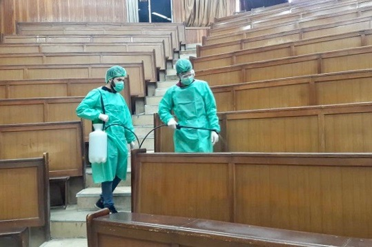 Two workers sanitize the seats in a Damascus University lecture hall (Photo: Ministry of Higher Education Facebook page).