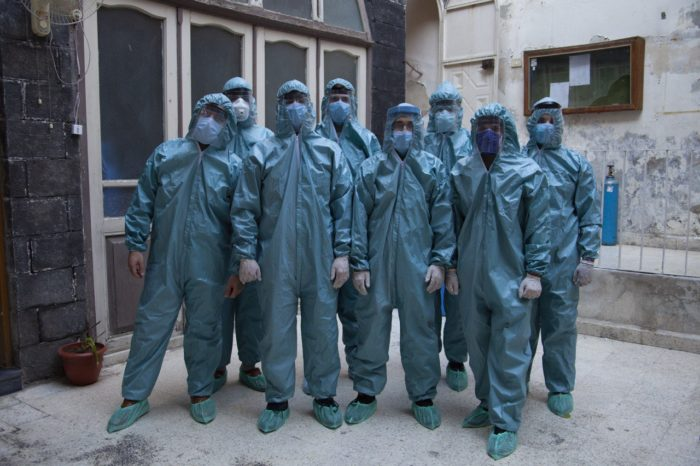 """Members of the """"Sanitize It"""" team don protective suits for a group photo outside their headquarters in Damascus. The team took its services to more than 1,000 patients in homes this summer (Photo by Omar Malas)."""