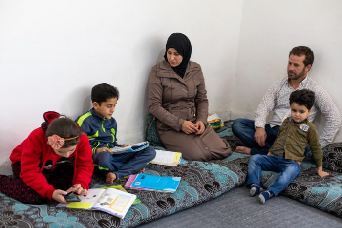 Ghazal, 11, uses a mobile phone to study in her Syrian refugee family's home in Jordan. With her are her mother and father, Salwa and Naeem, and brothers Omar, 9, and Mohammad, 4  (Photo: UNHCR/Lily Carlisle).